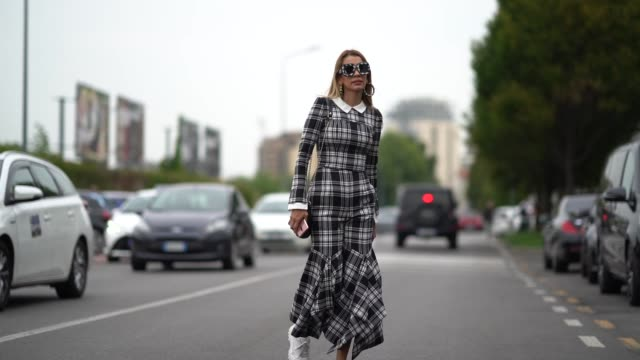 vídeos de stock e filmes b-roll de guest wears sunglasses, large earrings, a checked pattern jumpsuit with white collar, a bag, white sneakers, outside the prada show during milan... - ténis calçado desportivo