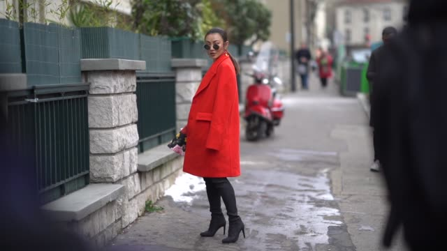 A guest wears sunglasses large earrings a red top an orange coat a multicolor floral print black Aline skirt black leggings black pointy toe shoes a...