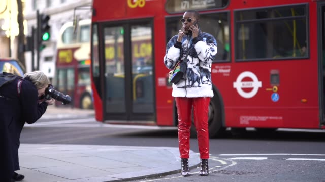 stockvideo's en b-roll-footage met guest wears sunglasses, red pvc pants, studded black leather shoes, a colored coat, a colored bag, during london fashion week men's january 2018 on... - materiaal