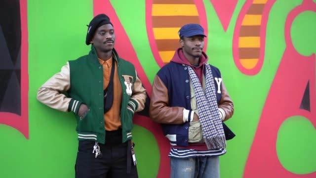 A guest wears wears a black beret hat a green jacket a guest wears a blue cap a blue jacket during London Fashion Week Men's January 2018 on January...