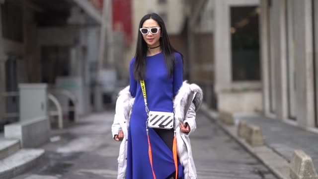 A guest wears white sunglasses an offwhite furlined hooded parka a deep purple long asymmetric and front slit long dress tied by a bow a black...