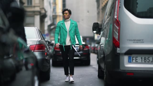 A guest wears yellow sunglasses a blue leather jacket a white turtleneck cropped pants white sneakers during Milan Fashion week Fall/Winter 2018/19...