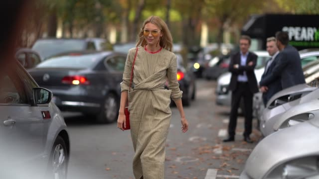 A guest wears yellow sunglasses sandcoloured striped dress with a red collar white ankle boots outside the Rochas show during Paris Fashion Week...