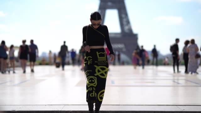 stockvideo's en b-roll-footage met a guest wearssunglasses a cropped bare belly turtleneck top a skirt with yellow prints outside offwhite during paris fashion week menswear... - coltrui