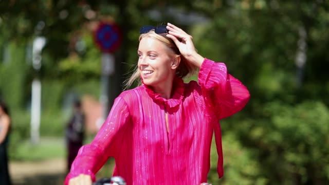 vídeos y material grabado en eventos de stock de guest with her bike wearing a pink dress during the copenhagen fashion week spring/summer 2019 on august 9, 2018 in copenhagen, denmark. - copenhague