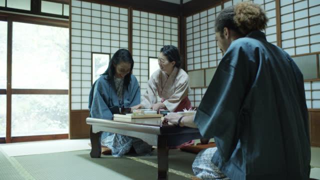 vídeos de stock, filmes e b-roll de os hóspedes e hostess que se curvam e sorriem como refeição são servidos no ryokan - washitsu