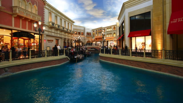guests at the venetian casino ride in gondolas or browse at shops. - venetian hotel las vegas stock videos & royalty-free footage