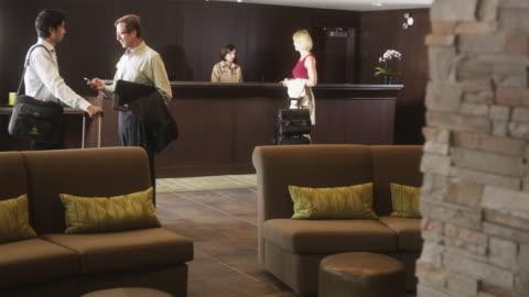 vídeos de stock, filmes e b-roll de ws guests checking-in at hotel reception desk / squamish, british columbia, canada - mala de rodinhas