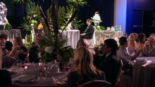 dolly ws guests enjoying themselves at their tables, with bride, groom, best man, and maid of honor at wedding table on stage - festlich gekleidet stock-videos und b-roll-filmmaterial