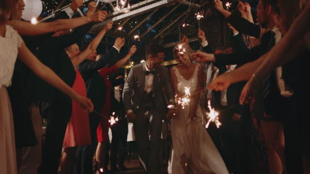 vidéos et rushes de invités retenant des cierges magiques au-dessus des jeunes mariés courant - jeunes mariés