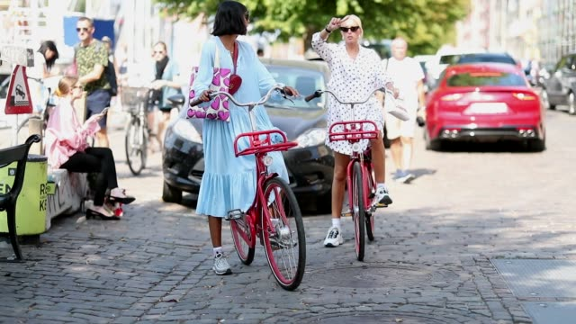 Guests on bicycles are seen during the Copenhagen Fashion Week Spring/Summer 2019 on August 9 2018 in Copenhagen Denmark