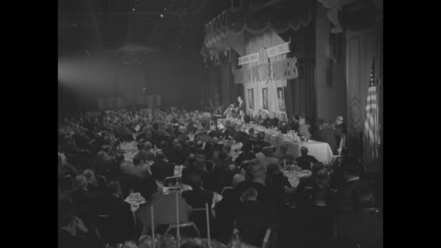 wv guests seated at tables head table to right / guests seated at head table look to right at speaker at podium / harry cohn holds plaque hands it to... - warner bros stock videos & royalty-free footage