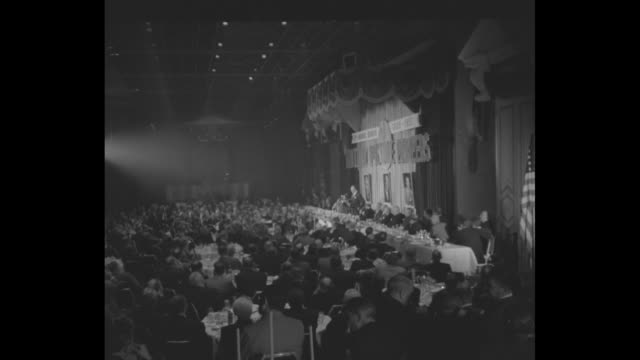 guests sit at tables in starlight roof room of waldorf astoria hotel head table with distinguished guests at right / men at head table looking at... - warner bros stock videos & royalty-free footage