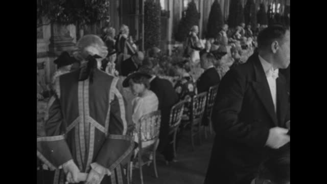 Guests standing at long table with decorations on it in the Palace of Versailles' Hall of Mirrors / guests including George VI of the UK French...