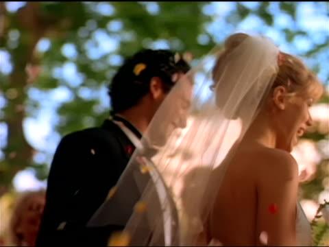 guests throw flower petals at a bride and groom. - blütenblatt stock-videos und b-roll-filmmaterial