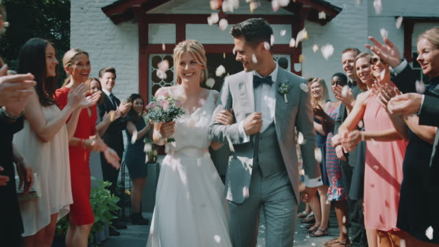 guests throwing petals over couple leaving church - ceremony stock videos & royalty-free footage