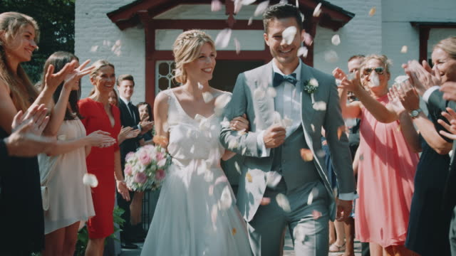 guests throwing petals over couple outside church - wedding stock videos & royalty-free footage