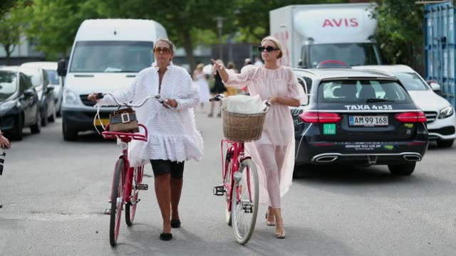 Guests walking with their bike during the Copenhagen Fashion Week Spring/Summer 2019 on August 8 2018 in Copenhagen Denmark