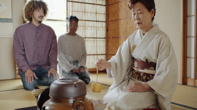 guests watching hostess preparing tea at traditional japanese ceremony - washitsu stock videos and b-roll footage