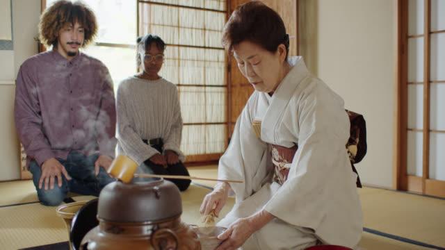vídeos de stock, filmes e b-roll de convidados que prestam atenção à hostess whisk tea na cerimónia japonesa tradicional - washitsu