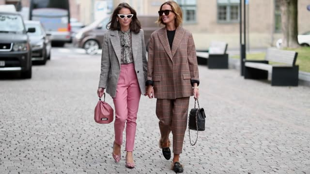 Guests wearing grey blzaer jacket and pink pants and a beige checked suit during Oslo Runway SS19 on August 15 2018 in Oslo Norway