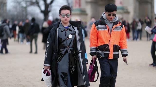 Guests wearing orange jacket and black coat outside Kenzo during Paris Fashion Week Menswear F/W 20192020 Day Sixon January 20 2019 in Paris France
