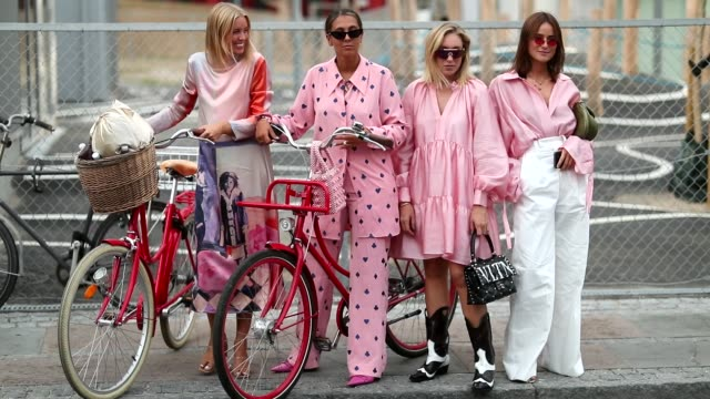 Guests wearing pink with their bikes during the Copenhagen Fashion Week Spring/Summer 2019 on August 8 2018 in Copenhagen Denmark