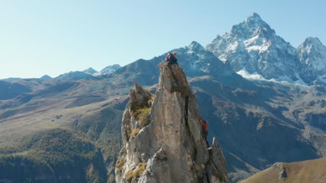 vídeos de stock e filmes b-roll de guide leads female mountaineer up high pinnacle - confiança