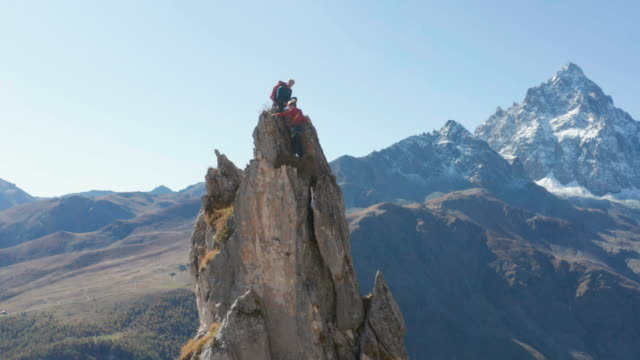 stockvideo's en b-roll-footage met guide leads female mountaineer up high pinnacle - trust