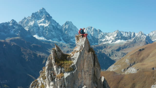 guide leads female mountaineer up high pinnacle - on top of stock videos & royalty-free footage