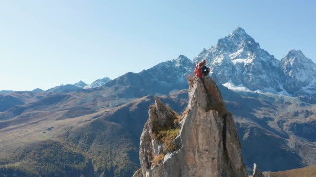 guide leads female mountaineer up high pinnacle - emozione positiva video stock e b–roll