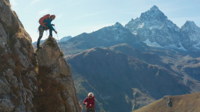 guide leads female mountaineer up high pinnacle - vertrauen stock-videos und b-roll-filmmaterial