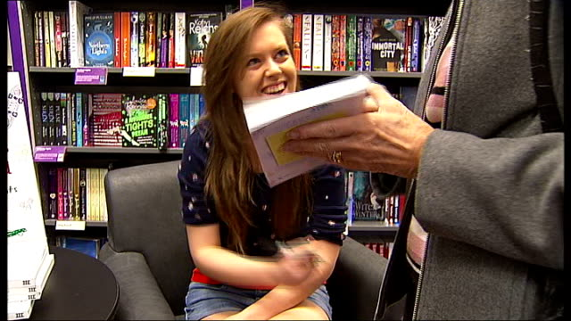 vidéos et rushes de guide to teenagers for parents written by schoolgirls england surrey sutton int general views of customers reading book / customer talking to louise... - store