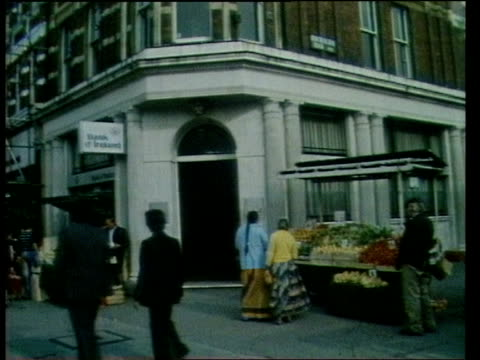 Guilford Four Case TX 221075 London Kilburn High Rd TGV Street as shoppers traffic to fro MS Fruit stall at corner as shoppers past in f/g MS Old man...