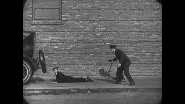1921 guilty man (buster keaton) hides under car before being driven away pursed by a crowd of police officers - dragging stock videos & royalty-free footage