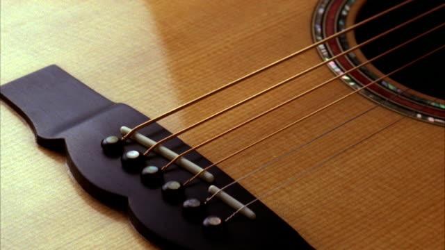 vídeos y material grabado en eventos de stock de a guitar has bridges under the strings. available in hd. - instrumento de cuerdas
