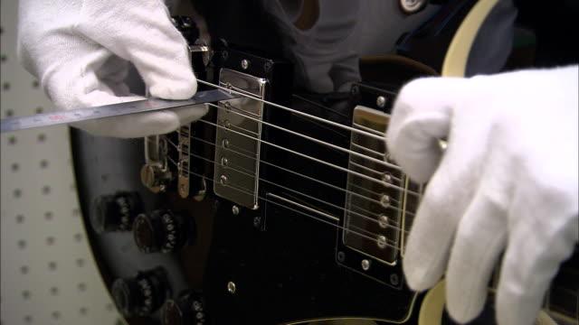 vídeos y material grabado en eventos de stock de a guitar maker fine tunes the fret on an electric guitar. - diapasón instrumento de cuerdas
