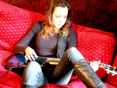 guitar playing woman sitting and strumming - pants stock videos and b-roll footage