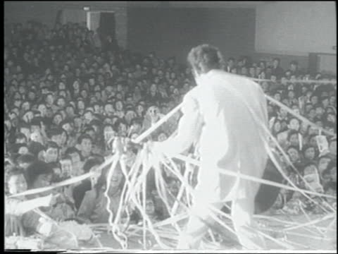b/w 1958 newsreel rear view guitarist in rockabilly band on stage in concert / tokyo - klassischer rock and roll stock-videos und b-roll-filmmaterial