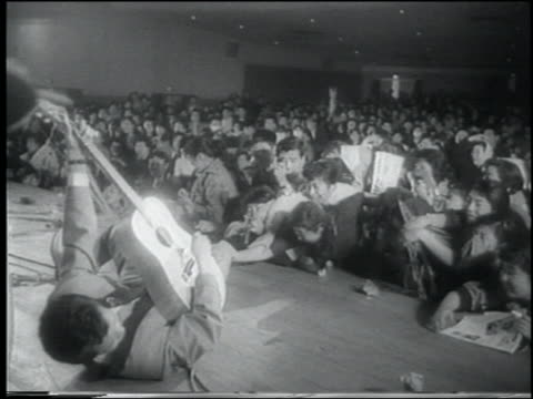 vídeos de stock e filmes b-roll de b/w 1958 newsreel rear view guitarist in rockabilly band playing on back in concert / tokyo - rocking
