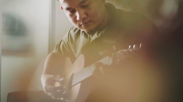 vídeos de stock, filmes e b-roll de guitarrista é tocar guitarra enquanto usa capo - dedilhando instrumento