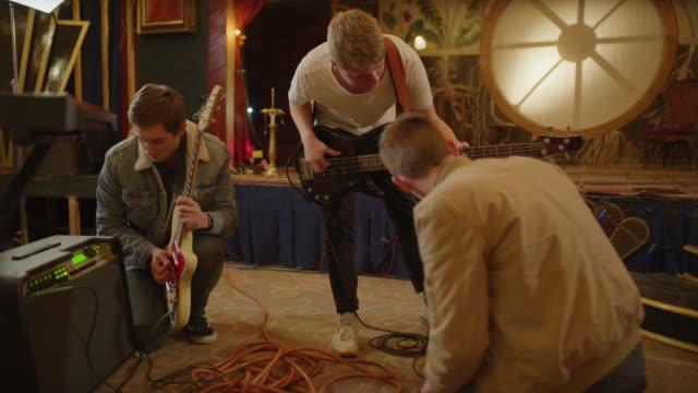 vídeos de stock e filmes b-roll de guitarists adjusting amplifiers and tuning guitars in nightclub / provo, utah, united states - provo