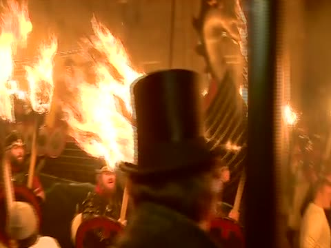 vídeos de stock, filmes e b-roll de guizers with flaming torches drag a replica viking galley for the up helly aa festival - festival tradicional