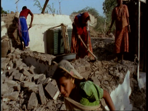 ms gujarat, indian family clearing house demolished by earthquake, gujarat, india - グジャラート州点の映像素材/bロール