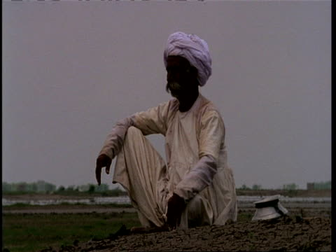 MCU Gujarat, Indian herdsman sitting on ground looking out, Gujarat, India