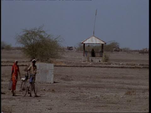 MS Gujarat, Indian people walking through desert camp, pushing bike, Gujarat, India