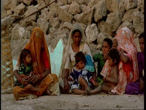 ms gujarat, indian women and children sitting amongst ruins of house, after earthquake, gujarat, india - グジャラート州点の映像素材/bロール