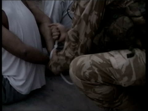 day 10 evening news iraq umm qasr ext british royal marines kicking down door and rushing into house in dawn raid to seize saddam hussein loyalists... - prisoner stock videos & royalty-free footage