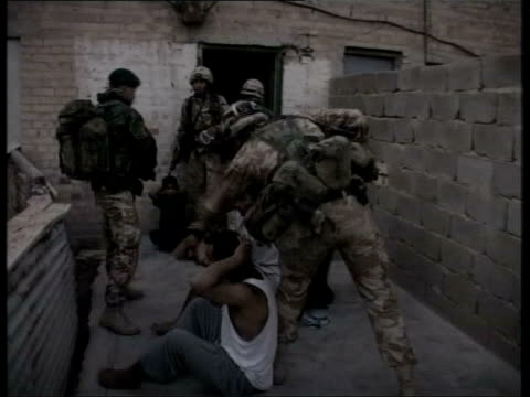 news at ten; pool iraq: umm qasr ext british royal marines kicking down door and rushing into house in dawn raid to seize saddam hussein loyalists... - basra stock-videos und b-roll-filmmaterial