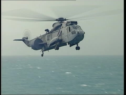 day 3 lunchtime news bulletin evening sea king helicopter flying along gv royal navy sea king helicopter flying along pan crew members dragging... - warship stock videos & royalty-free footage